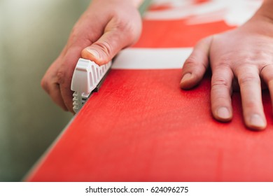 hands sharpening and waxing red snowboard very careful