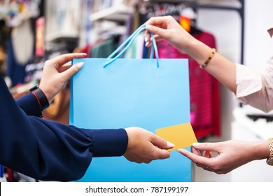 Hands with shopping bag and credit card close up -  buy-sell concept image.