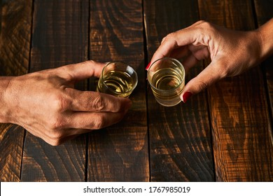 Hands with shot glasses toasting. Concept of alcoholism and addiction.