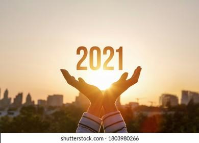 Hands zeigen Neujahr 2021 vor dem Hintergrund der Sonne.