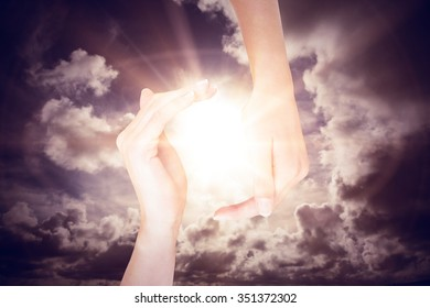Hands showing against dark sky with white clouds