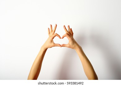 Hands showing heart of the fingers on a white background
