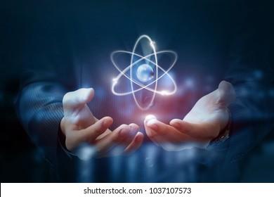 Hands shows the atom on a dark blurred background.