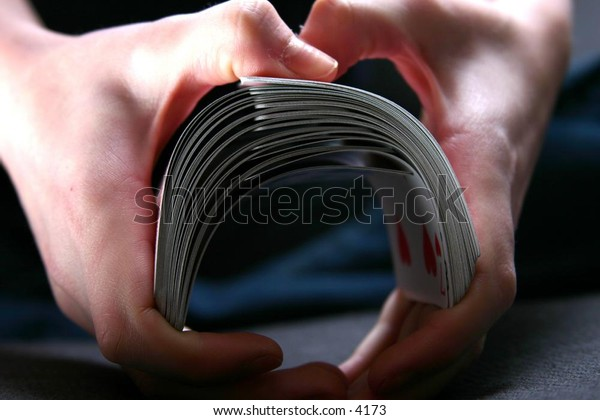 hands shuffle a deck of cards