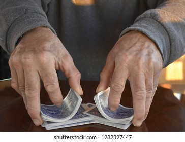 Hands shuffling a deck of cards for a game of rummy