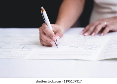 hands signing a paper in a wedding ceremony