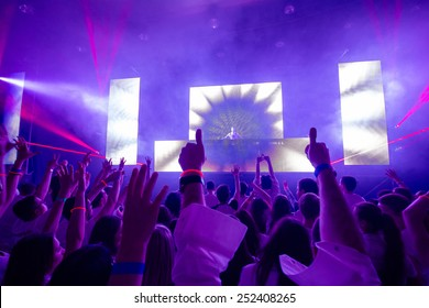 Hands silhouette on a concert in the center  - DJ visible on the stage. Pink rays laser show.