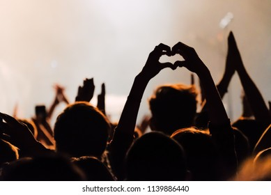 Hands silhouettes of the crowd raised up at music show. Heart made by fingers