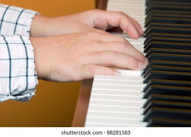 hands from a six years old boy on a piano
