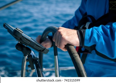 Hands of the skipper at the helm control of sailing boat
