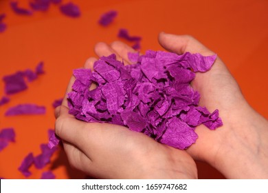In the hands of small pieces of purple paper. Children's hands on an orange background. Fun game.