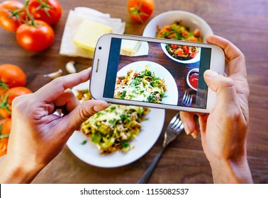 Hands with the smart phone pictures of meal. Young woman, cooking blogger is cooking at the home kitchen in sunny day and is making photo at smartphone. Instagram food blogger workshop concept.