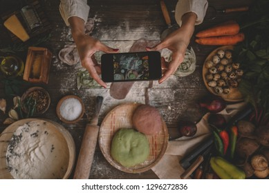 Hands with the smart phone pictures of meal. Young woman, cooking blogger is cooking at the home kitchen and is making photo at smartphone. Instagram food blogger workshop concept.