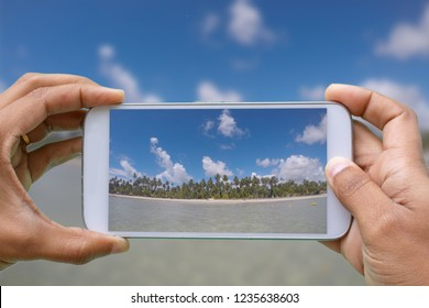 hands with smartphone photographing Carneiros Beach - Tamandare -Pernambuco - Brazil. Beach of warm waters with many palm trees and blue sky with clouds