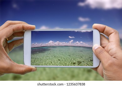 hands with smartphone photographing Patacho Beach, Porto de Pedras, Alagoas, Brazil