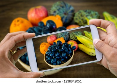 hands with smartphone photographingblack grape under wooden table with other fruits like banana, apple and orange - one of the most delicious fruits