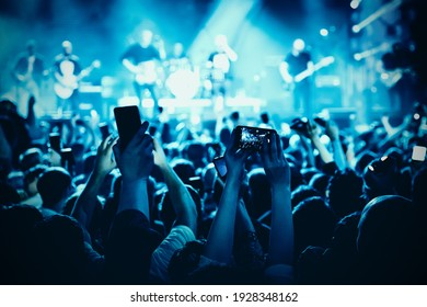 A lot of hands with the smartphone turned on to record or take pictures during the live concert - Shutterstock ID 1928348162
