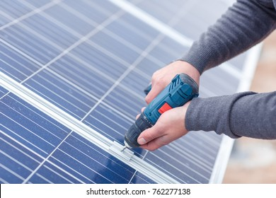 The hands of the solar battery station worker drills the panel. Close-up. Outdoors.