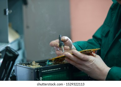 Hands solder a soldering iron board