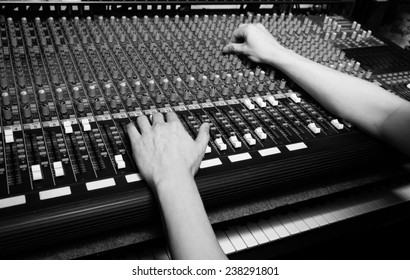 hands of sound engineer working on recording studio mixer. bw filter