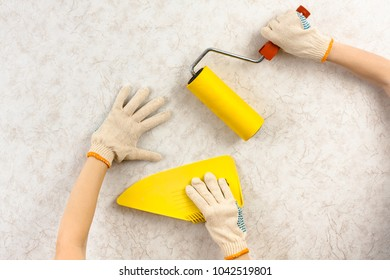 hands with spatula and roller smoothing wallpaper on the wall