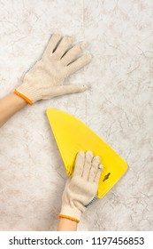 hands with spatula smoothing wallpaper on the wall during repair