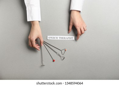 Hands of speech therapist with logopedic probes on grey background