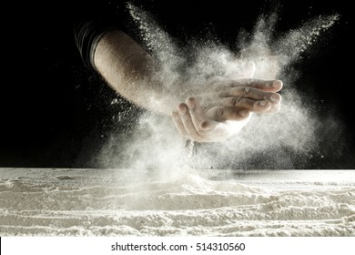 hands with splash of white flour and black background