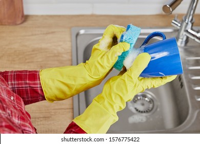 Hands with sponge wash the cup under water, housewife woman in yellow rubber protective gloves washing blue mug in a kitchen sink with a blue sponge, Hand cleaning, manually, housework dishwasher