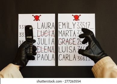 hands of the stalker wrapped in gloves black with the phone   are the sign of a threat of death for women whose names appear on the list