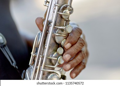Hands of a street muscian playing a Saxaphone with shallow depth of field