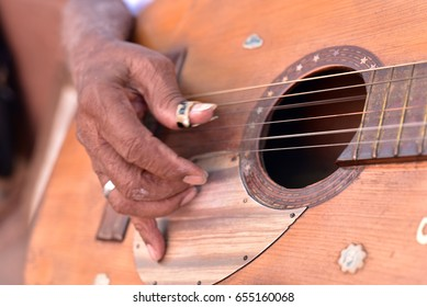 Hands of the street musician playing the guitar at Trinidad, Cuba