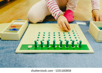 Hands of a student boy using wooden material in a Montessori school.
