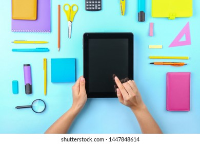 Hands of student with tablet computer and stationery on color background