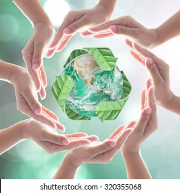 Hands surrounding green planet protected by recycle sign leaf on blurred bokeh .Elements of this image furnished by NASA