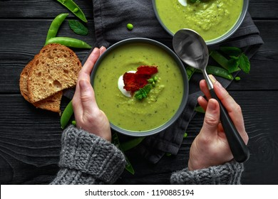 Hands in sweater, pullover holding cosy warming in cold weather. Sweet pea, leek and mint hot soup topped with crunchy bacon and dolop of yogurt