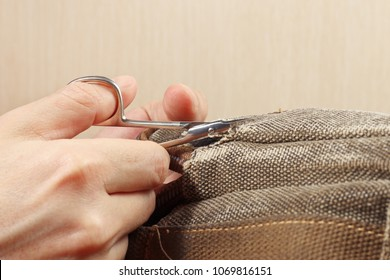 Hands of tailor with a pair of scissors cut a strong cloth close up