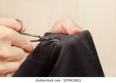 Hands of tailor with a pair of scissors cut a gray jacket cloth close up