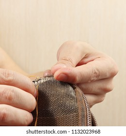 Hands of tailor repair durable cloth bag with a needle close up