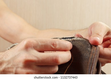 Hands of tailor sew durable cloth bag with a needle close up