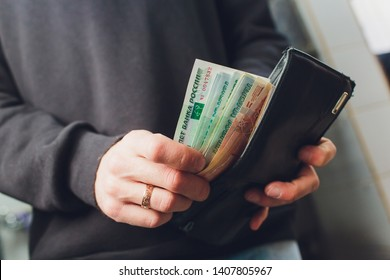 Hands take out russian rubles from wallet. Closeup on a man's hands as he is getting a banknote out of his wallet.