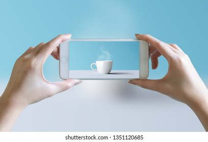hands take photo of cup of coffee and aroma smoke with mobile smartphone