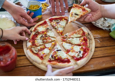 hands take slices of pizza