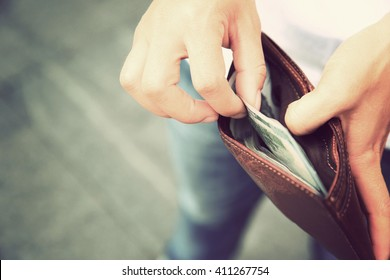 Hands taking out money from wallet on street
