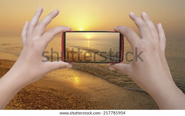 Hands taking photo beach with smartphone