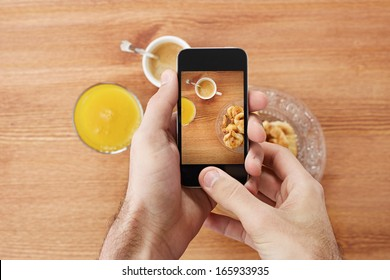 Hands taking photo of breakfast including croissants, cofee and orange juice with smartphone