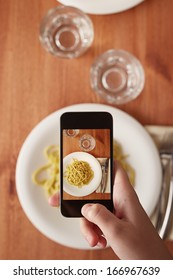 Hands taking photo of Italian pasta lunch with smartphone