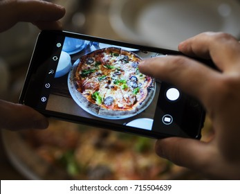 Hands taking picture of delicious pizza with smartphone