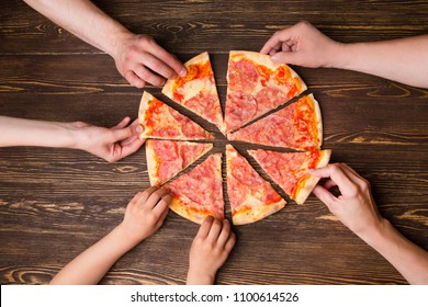 Hands taking pizza slices from wooden table, close up view