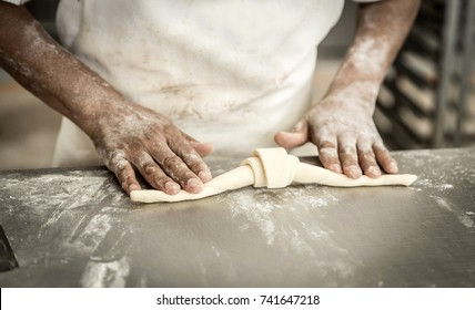hands of the teacher baker in the bread production on the table